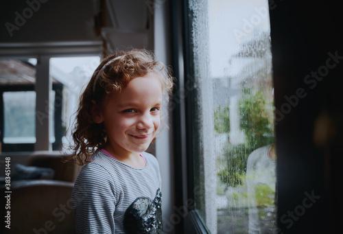 Photo Portrait of smiling school girl standing near window with rain drops on window i