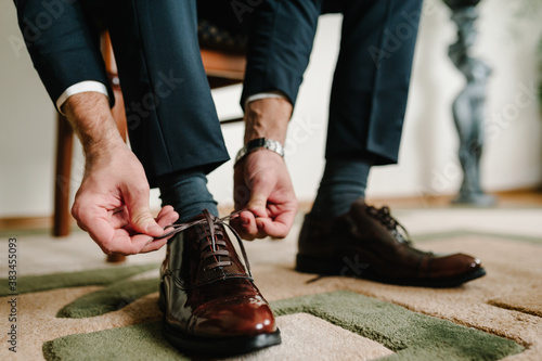 Fototapeta The groom morning before wedding ceremony wears shoes. Businessman tie the laces on the shoes. Men's style. Professions. To prepare for work, to the meeting. obraz