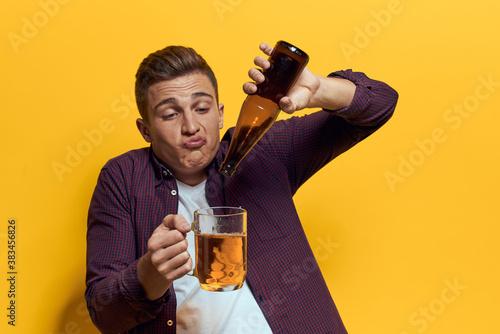 cheerful man mug of beer with bottle fun drunken lifestyle alcoholic yellow back Fototapet