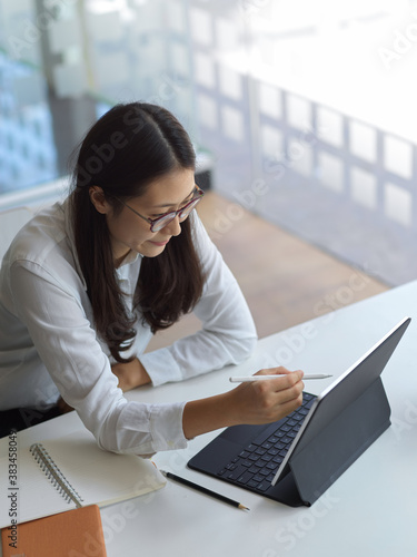 Businesswoman working on her project while using tablet in workspace Canvas Print