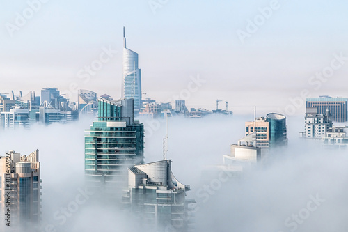 Fototapeta Morning fog hovering skyscrapers at sunrise. Building rooftops over the clouds in Dubai Marina