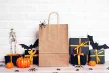 Brown Paper Shopping Bags With Halloween Decorations On White Brick Wall Background. Copy Space For Text.