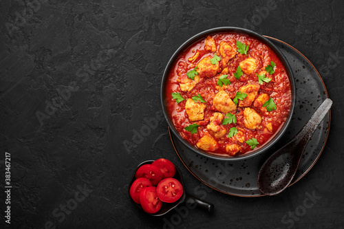 Fotomural Chicken Madras Curry in black bowl on dark slate table top