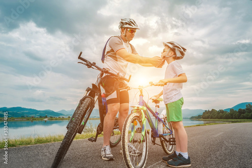 Foto Father and son ride, cycling their bikes together, on sunny day, Happy family in helmets is riding bikes having fun