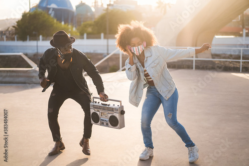 Foto African friends dancing together while listening music with boombox - Focus on w
