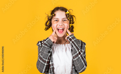 Photo Girl with curlers and hair clips in her hair on yellow background