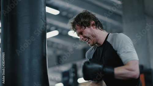 Aggressive kickboxer showing strength at gym Fotobehang