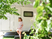 Girl In A Caravan On A Camping Site. She Is On Vacation.