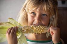 Young Girl Eating Yellow Corn ...