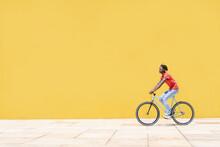 Black Guy Riding Bicycle Near Wall