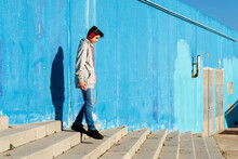 Teenage Boy Walking Down Steps While Listening To Music On Smartphone