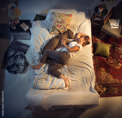 Fotografie, Tablou Portrait of a woman, female breeder sleeping in the bed with her dog at home