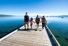 A Family Walks On A Pier On A Beautiful Day In South Lake Tahoe, CA