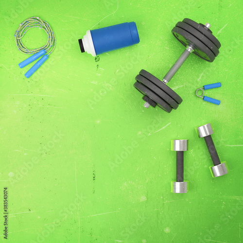 Gym fitness sport background. Flat lay template with weight dumbell, shaker, jumping rope isolated on green background. Fit sport concept mockup. 3D rendering.