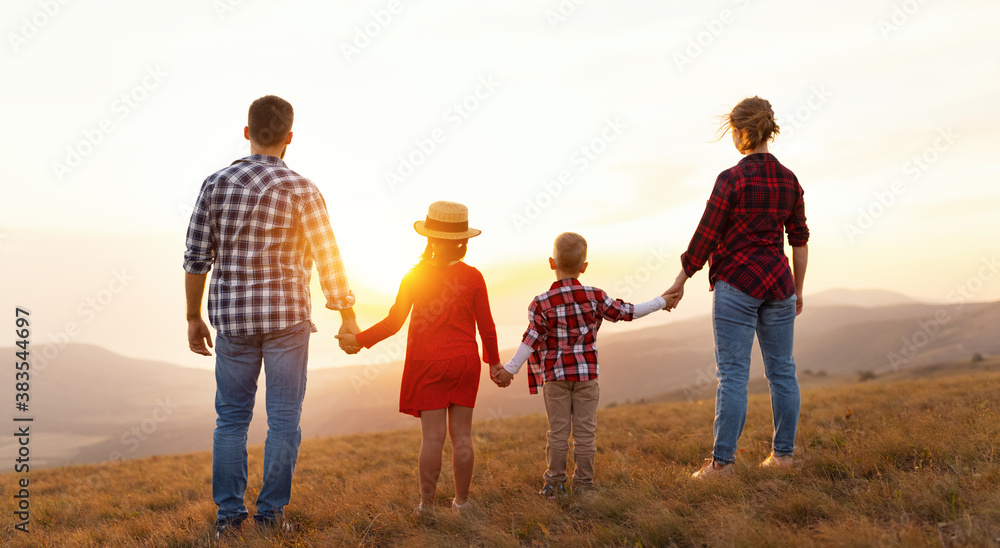 Fototapeta Happy family: mother, father, children son and daughter stand with their backs holding hands on  sunset.