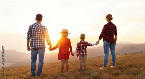 Happy family: mother, father, children son and daughter stand with their backs holding hands on  sunset. - 383544697