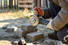 A Man Saws Off Paving Stones With An Angle Grinder. Street Work