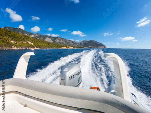 Baunei, Italy 28/07/2020; The stern of a dinghy boat at high speed navigation powered by a Honda 200 hp outboard engine, in the background the Sardinian coast of the Gulf of Orosei.