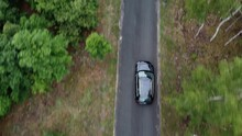 Black Car Driving On A Road. With A Droneshot Above The Cars Head.