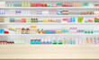 Leinwandbild Motiv Empty wood counter top with pharmacy drugstore shelves blur pharmaceutical medicine product background