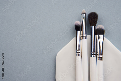 Obraz makeup brushes on gray background and stand cropped view Copy Space - fototapety do salonu