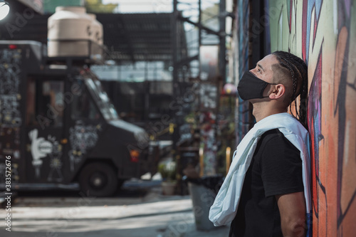 Fototapeta Mexican young man leaning on the wall, urban portrait wearing face mask obraz
