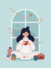 Woman drinking a cup of cocoa sitting near the Christmas gifts