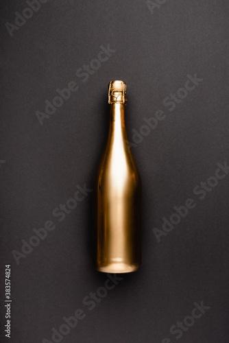 Obraz na plátně Top view of golden bottle of champagne on black background