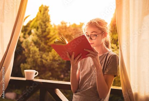Vászonkép Caucasian teenage girl reading book outdoor on the garden terrace while sunset