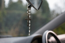 Rosary Beads Hanging On The Rear View Mirror Of Car
