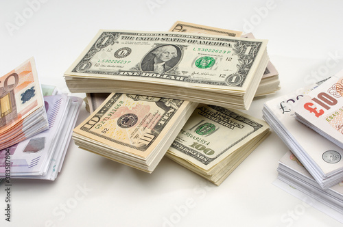 Cuadros en Lienzo Stack of US, British and European currency over white background