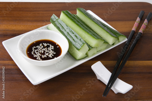 Soy Sauce With Cucumber Slices And Chopsticks On Table