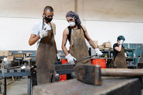 Canvastavla Serious men in aprons in workshop