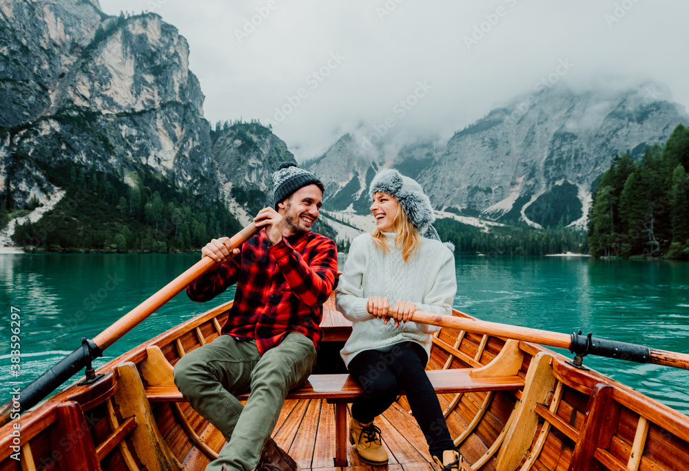Fototapeta Titolo: Romantic couple on a boat visiting an alpine lake at Braies Italy. Tourist in love spending loving moments together at autumn mountains. Concept about travel, couple and wanderust.