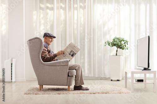 Fotomural Elderly man sitting in an armchair and reading a newspaper in a living room