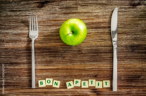 Fotografia Silverware and apple on wooden table with Bon apetit sign