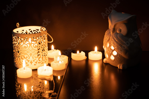 Fototapeta Intrincate metal candle holder with a lighting scented candle are displayed on the blak stone table in the dark living room of the house