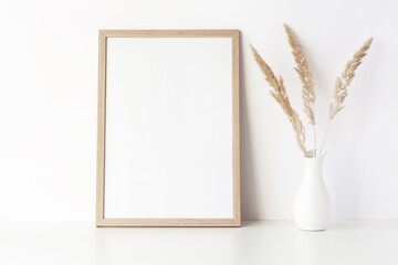 Empty wooden frame stands on white table with dry grass in vase. Mockup poster frame close up in home interior.