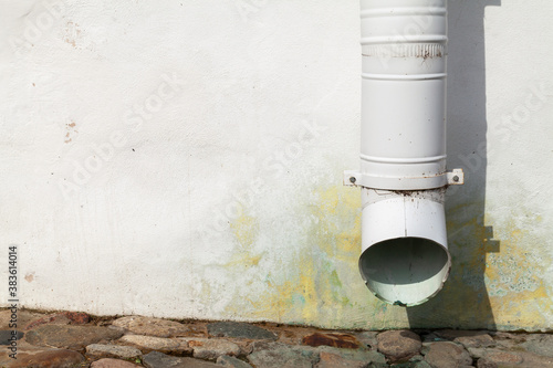 Fototapeta White drainpipe and old house wall, close-up