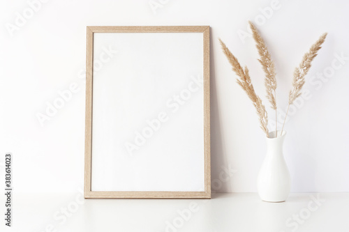 Obraz na plátně Empty wooden frame stands on white table with dry grass in vase