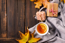 Autumn Still Life With Cup Of Tea, Pumpkins And Leaves On Wooden Background
