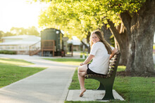 Teenage Girl Seated On Park Be...