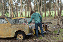 Person Looking At Old Junk Cars
