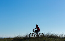 Silhouette Of Boy On Bike With...