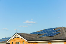Solar Panels Covering Tiled Roof Of Townhouse