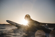 Silhouette Of Woman Surfing At...