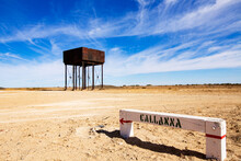 Sign And Water Tank Under Blue Sky With Wispy Clouds