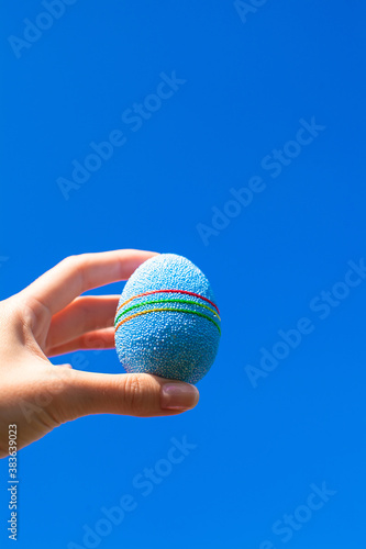 Bright Beautiful Easter egg in hand on background of blue sky