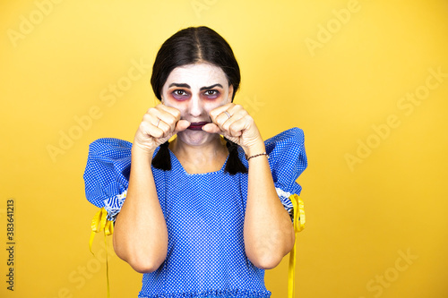 Foto woman wearing a scary doll halloween costume over yellow background depressed and worry for distress, crying angry and afraid