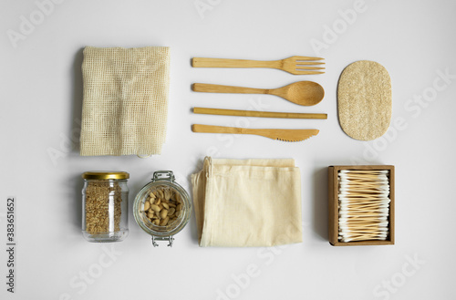 Obraz Zero waste kit. Set of eco friendly bamboo cutlery, mesh cotton bags, glass jars with a nuts, loofah sponge and box of cotton swabs. Natural and reusable items accessories on gray surface. - fototapety do salonu